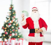 christmas, holidays, winning, currency and people concept - man in costume of santa claus with euro money over living room with tree