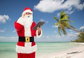 christmas, holidays, technology, travel and people concept - man in costume of santa claus with tablet pc computer over tropical beach background