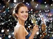 drinks, christmas, holidays and people concept - smiling woman in evening dress with glass of sparkling wine over snowy night city background