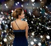 people, holidays, christmas and people concept - smiling woman in evening dress over snowy night city background from back