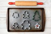 Overhead image of an old fashioned rolling pin and a cookie sheet with different holiday cookie cutters. Horizontal format on a rustic white wood kitchen table.