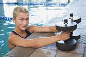 Portrait of a fit female swimmer with foam dumbbells in swimming pool at leisure centre