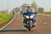 man riding a motorcycle on an open road