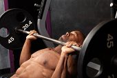 stock photo of weight lifter  - Weight lifter at the bench press lifting a barbell on an incline bench - JPG