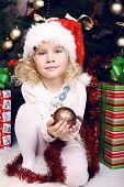 Cute Little Girl In Santa's Hat Sitting Beside A Christmas Tree