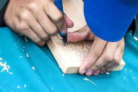 picture of woodcarving  - Knife in hands of the master woodcarving  - JPG