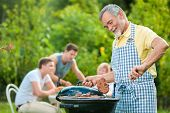 picture of bbq party  - Family having a barbecue party in their garden in summer - JPG