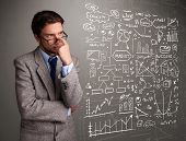 pic of anal  - Attractive young man looking at stock market graphs and symbols - JPG