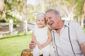 stock photo of granddaughter  - Loving Grandfather and Granddaughter Hugging Outside At The Park - JPG