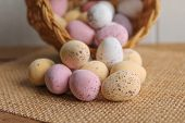pic of easter candy  - Pastel candy coated Easter Eggs in a wicker basket - JPG