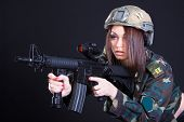 pic of assault-rifle  - Portrait of a woman in a military uniform with an assault rifle over black background - JPG