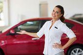 image of showrooms  - happy young saleswoman welcoming gesture in car showroom - JPG
