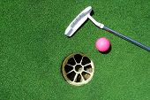 stock photo of ladies golf  - Golf club laying on green, pink golf ball, hole.
