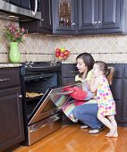 image of homemaker  - Pretty woman opening oven with a tray of cookies - JPG