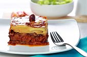 picture of greek  - portrait of Traditional Greek beef Moussaka with olive served in dish with fork aside - JPG
