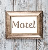 picture of motel  - Word Motel in frame on wooden background - JPG