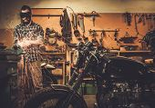 pic of rockabilly  - Mechanic doing lathe works in motorcycle customs garage  - JPG