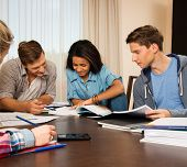foto of exams  - Multi ethnic group of students preparing for exams in home interior behind table  - JPG