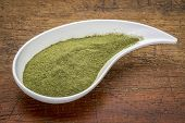 picture of teardrop  - organic wheatgrass powder on a white teardrop shaped bowl against rustic wood - JPG