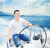 pic of sailing vessels  - A young and handsome Caucasian man sailing in the sea on a boat on a sunny day - JPG