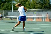 pic of youg  - youg girl swings her tennis racqet to return a ball back over the net - JPG