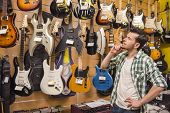 stock photo of guitar  - Young man is considering electric guitars music store - JPG