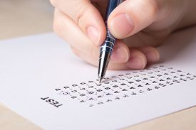 picture of bubble sheet  - female hand filling test score sheet with metal pen - JPG