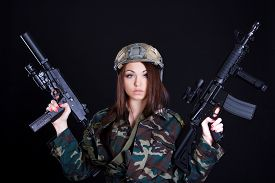 image of tommy-gun  - Portrait of a military woman with two guns over black background - JPG