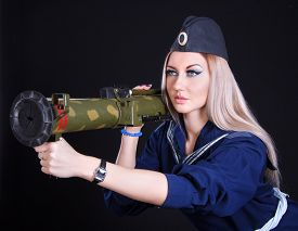 picture of grenades  - Beautiful young woman in a marine uniform with a grenade launcher over black background - JPG