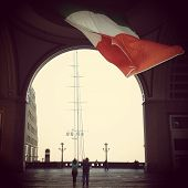 stock photo of irish  - Tourists looking at an Irish flag that flies over an archway - JPG