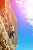 picture of climbing wall  - Young man climbs on a rocky wall - JPG