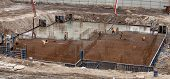 image of concrete pouring  - Construction of the building. Pouring the concrete foundation slab foundation. The concrete base slab foundation under the building. Stages of construction of the building. Foundation plate and armature. ** Note: Visible grain at 100%, best at smaller si - JPG