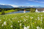 stock photo of bavarian alps  - wide panorama landscape in Bavaria Germany with farm house and chapel at lake with alps mountains - JPG