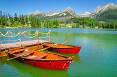 picture of mountain-high  - Red boats on the background of the high peaks of the Tatra Mountains and mountain lake - JPG