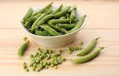 stock photo of green pea  - Green peas and pea pods in white dish on wooden tablecloseup - JPG