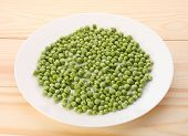 picture of green pea  - Green peas in white plate and on wooden tablecloseup - JPG