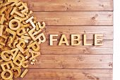 foto of fable  - Word fable made with block wooden letters next to a pile of other letters over the wooden board surface composition - JPG