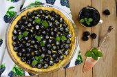 foto of blackberries  - Tart with cream and fresh blackberries on wooden table - JPG
