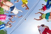 picture of volleyball  - View from below of kids playing volleyball on the game court outside during summer sunny day - JPG
