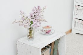 image of curio  - lilac bouquet and tea in china teacup on the vintage nightstand - JPG