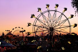 stock photo of carnival ride  - Silhouettes of carnival rides under the sunset - JPG