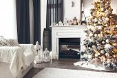 Beautiful holiday decorated room with Christmas tree, fireplace and armchair with blanket. Cozy wint poster
