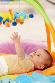 Baby reaching for colorful toy on playmat.?