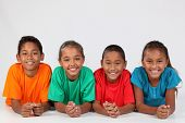 stock photo of ten years old  - Four young school mates lined up on the floor - JPG