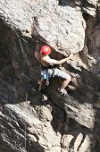 pic of sling bag  - A rock climber works his way up a rock face protected by a rope clipped into bolts - JPG
