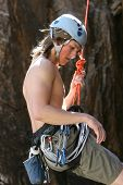 stock photo of sling bag  - A teenager is lowered down after completing a rock climb - JPG