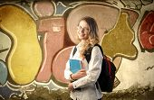Beautiful young student with wall full of graffiti on the background