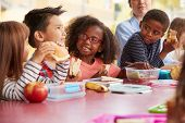 Young school kids eating lunch talking at a table together poster