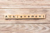 Achievement Word Written On Wood Block. Achievement Text On Table, Concept. poster