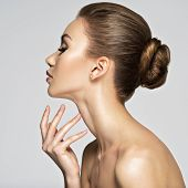 Beautiful woman cares for the skin neck- posing at studio isolated on white. Beauty treatment concep poster